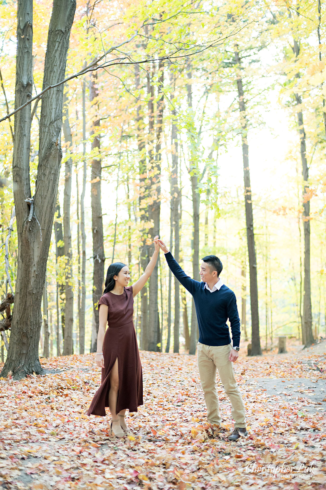 Christopher Luk Toronto Wedding Engagement Session Photographer Autumn Fall Leaves Natural Candid Photojournalistic Bride Groom Holding Hands Walking Together Pathway Hiking Trail Dancing Twirl Spin Trees