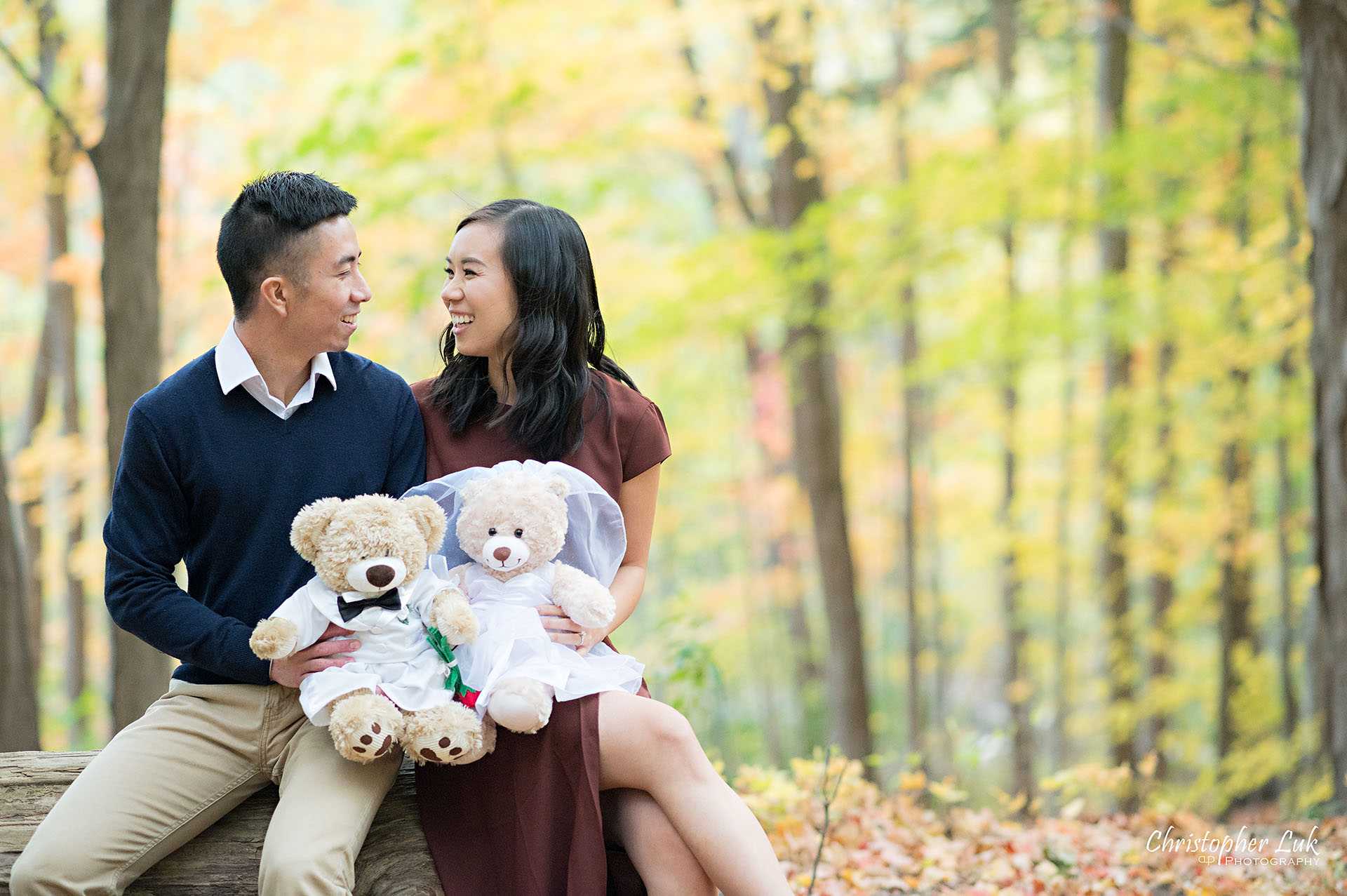 Christopher Luk Toronto Wedding Engagement Session Photographer Autumn Fall Leaves Natural Candid Photojournalistic Bride Groom Hiking Trail Stuffed Animal WongFu Productions Spencer Bear Trees Log Smiling Happy Together Landscape