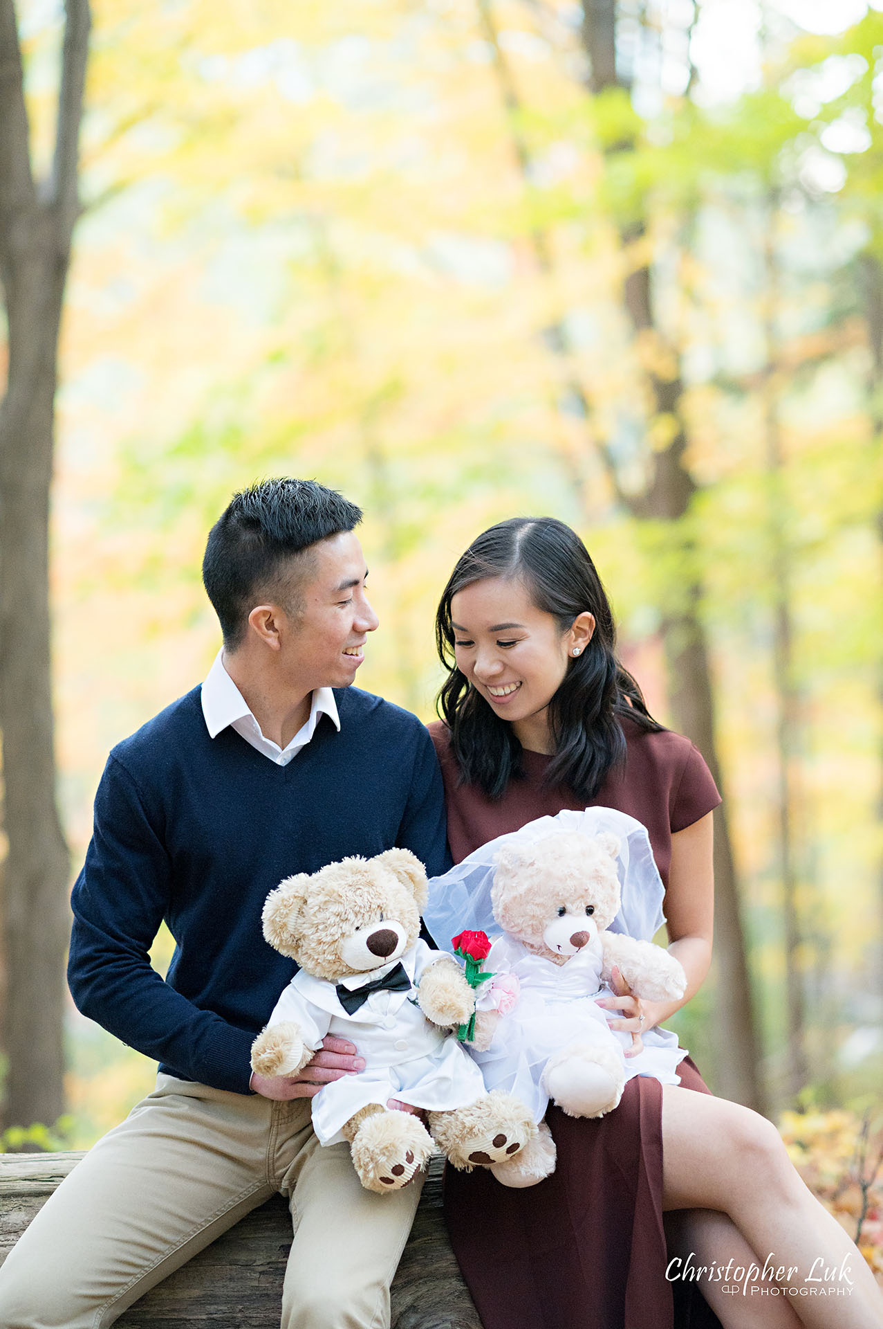 Christopher Luk Toronto Wedding Engagement Session Photographer Autumn Fall Leaves Natural Candid Photojournalistic Bride Groom Hiking Trail Stuffed Animal WongFu Productions Spencer Bear Trees Log Smiling Happy Portrait
