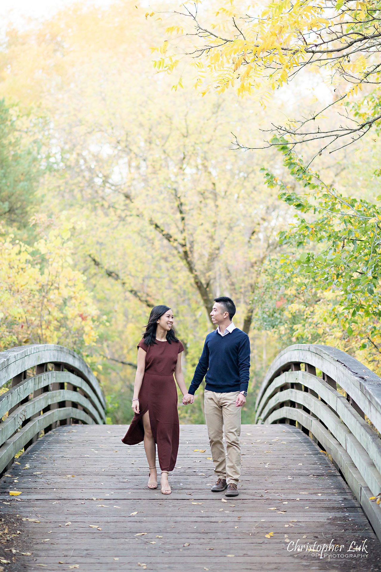 Christopher Luk Toronto Wedding Engagement Session Photographer Autumn Fall Leaves Natural Candid Photojournalistic Bride Groom Bridge Holding Hands Walking Together