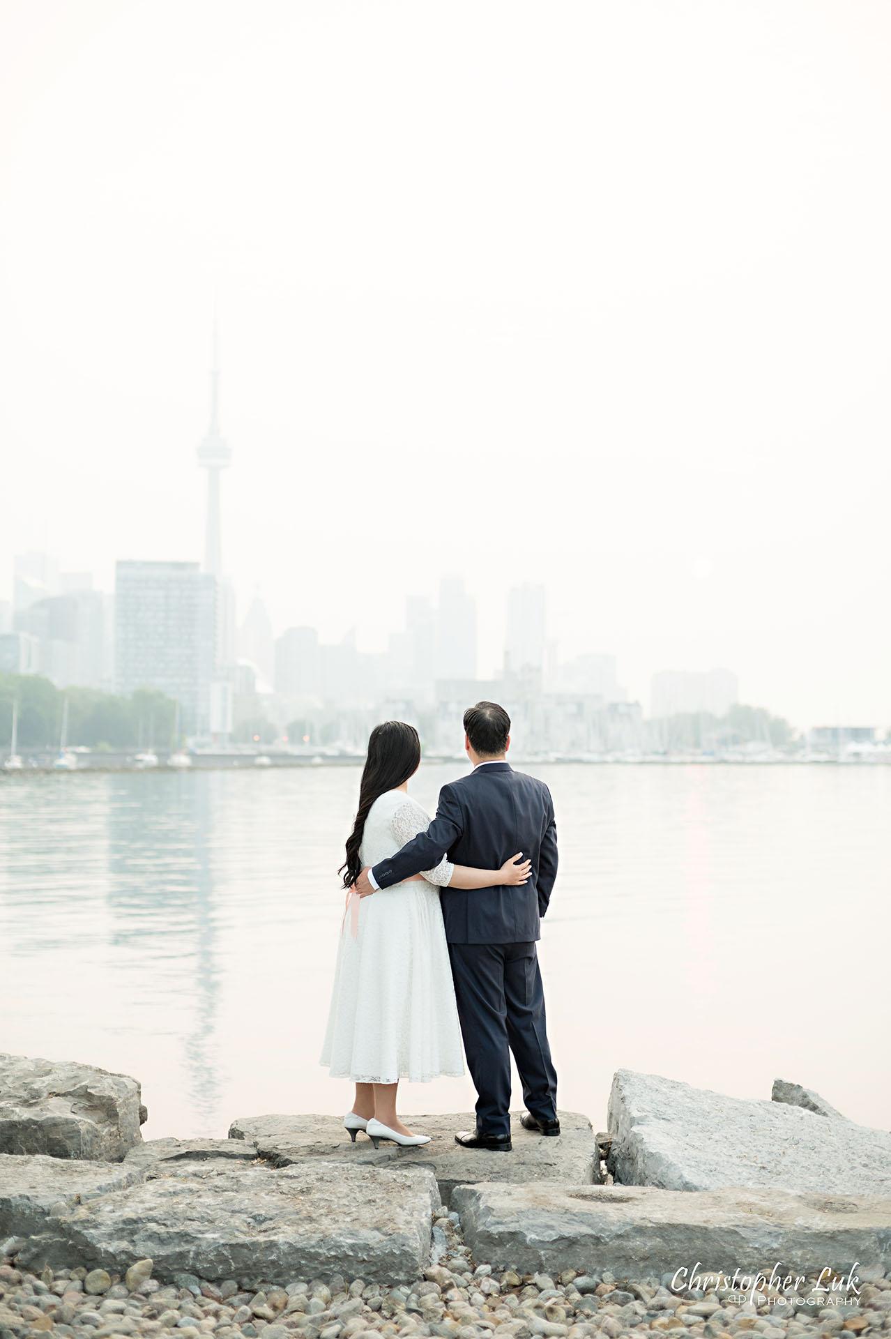 Christopher Luk Toronto Wedding Photographer Trillium Park Engagement Session Ontario Place Waterfront Skyline Natural Candid Photojournalistic Bride Groom Hug Together Loving CN Tower Portrait