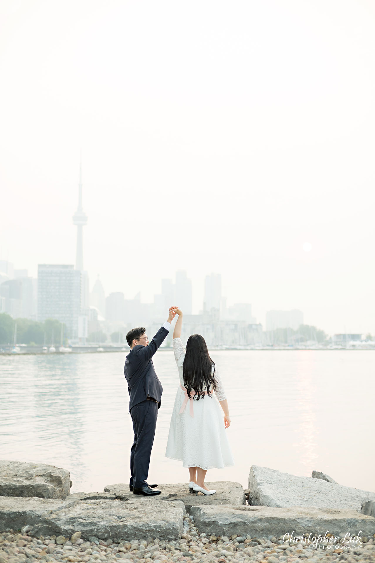 Christopher Luk Toronto Wedding Photographer Trillium Park Engagement Session Ontario Place Waterfront Skyline Natural Candid Photojournalistic Bride Groom Dancing Spinning Together Loving CN Tower